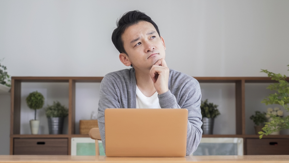 Asian,Man,Using,A,Computer,In,The,Living,Room